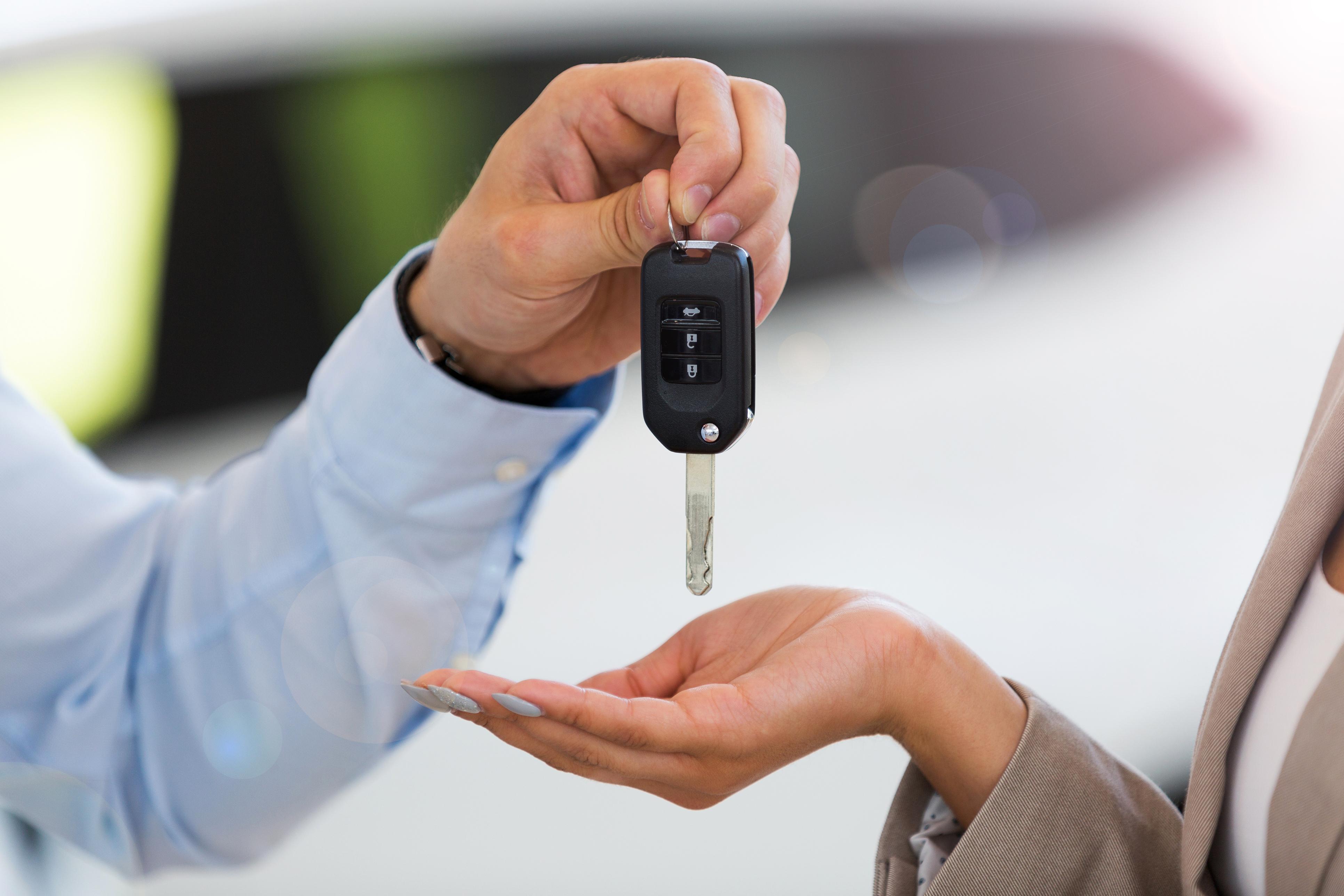 Car salesman handing car keys to woman in showroom